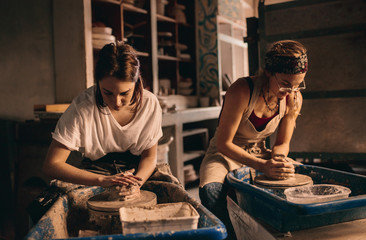 Two women at a pottery workshop making clay pots Wall mural