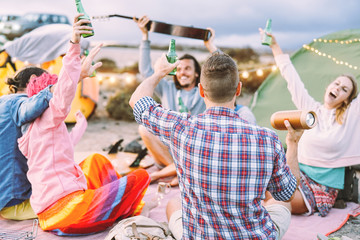 Happy friends making party drinking beers and playing music while camping with tents outdoor - Young people having fun and laughing together - Friendship, celebration, camp, lifestyle concept