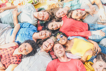 Group of diverse friends lying on grass having fun in a picnic in a park outdoor - Happy young multicultural people enjoying and laughing together - Concept of diversity, lifestyle, unity, friendship