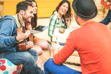 Group of friends having fun in living room in their home - Happy young people playing music with guitar and tablet singing and laughing together - Soft focus on male on left