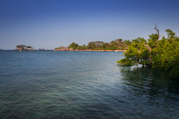 View of coastline on Nosy Komba Island lined with palm trees and boats floating in the sea, Madagascar