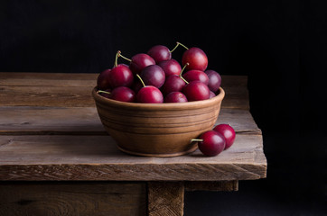 ripe plums in the bowl on wooden table