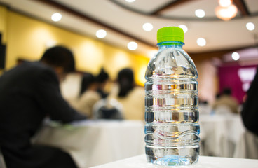 bottle water on desk in conference hall meeting room with light flare, business concept