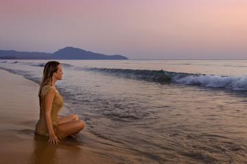 a girl meditating on the ocean shore