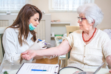 Nurse injecting vaccine to senior's woman arm.