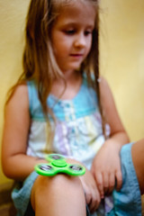 Little girl playing with green fidget spinner toy to relieve stress at home.