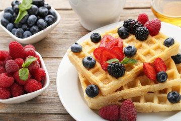 Sweet waffle with berries on grey wooden table