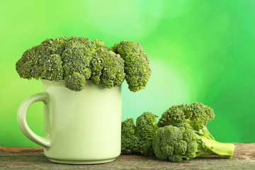 Broccoli in mug on wooden table