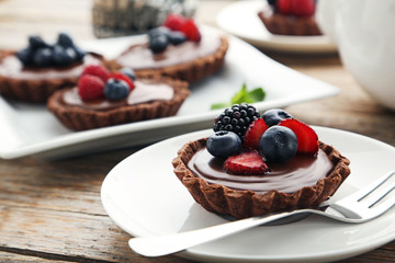 Chocolate tartlets with berries on grey wooden table