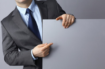 Businessman holding a blank board standing on gray background