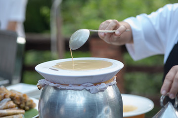 Hand of chef to Cook and pastry-cook in Thai food. Outdoor restaurant. Asian style.