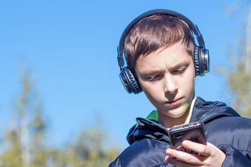 A teenager in a black jacket with headphones looks seriously at the smartphone in the park on a blue sky background.