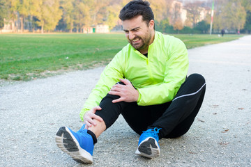 Male athlete suffering from pain in leg while exercising outdoors