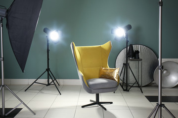 Interior of modern photo studio with armchair and professional equipment