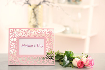 Frame with text MOTHER'S DAY and flowers on table