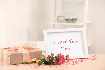Frame with text I LOVE YOU MOM, gift box and flowers on table