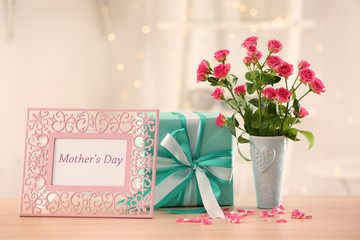 Gift box, flowers and frame with text  MOTHER'S DAY on table