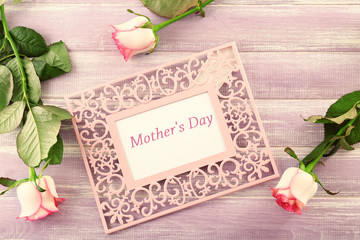 Frame with text MOTHER'S DAY and flowers on wooden background