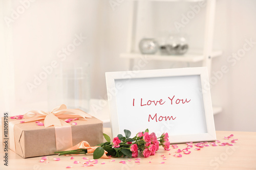 Frame with text I LOVE YOU MOM, gift box and flowers on table\
