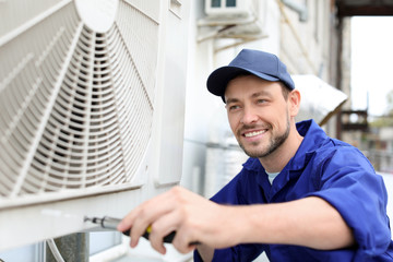 Male technician repairing air conditioner outdoors Wall mural