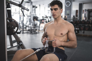 Rowing young man in gym training shirtless indoors