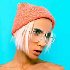 Cute Blonde Model in stylish accessories. Beanie and glasses. Casual fashion look