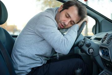 Man falling asleep in car after long hour drive needs a break