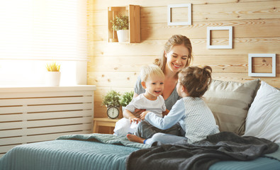 happy family mother and children in bed