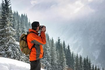 A man photographes of a winter, mountain landscape. Against the background of mountains and pines. Pictured from the back