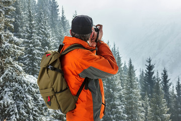 A man photographes a winter landscape. Against the background of mountains and pines. Pictured from the back