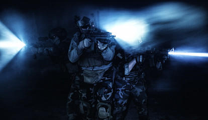 Squad of soldiers attacking in action under cover of darkness back light