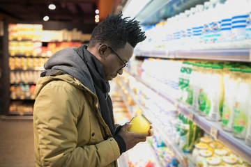 African man holding and choice butter in supermarket showcase