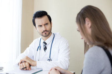 Attractive Doctor working at hospital. Doctor looking to woman with serious emotion.