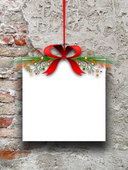 Blank Christmas square frame hanged by red ribbon against brick wall background