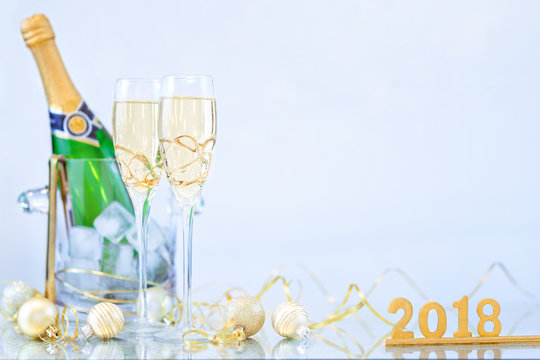 New Year Celebration with Champagne Glasses and a Bottle 2018. New Year flutes with bubbling champagne and a bottle on the blue background.