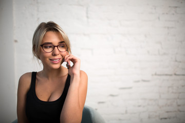 Charming smiling woman secretary talking on mobile phone during work break in company. Young blonde female entrepreneur having cell telephone conversation standing in office near copy space