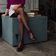 Female legs in short skirt and black pantyhose sitting on wooden box near big books . Soft focus photo.