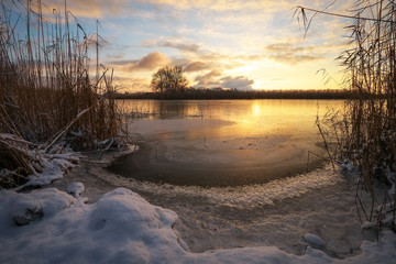 Winter landscape with sunset sky and frozen river. Daybreak