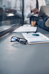 Office routine. Close-up of stylish glasses and folder are on windowsill. Professional african manager is working on laptop in background. Copy space