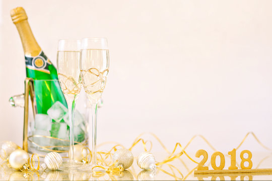 New Year Celebration with Champagne Glasses and a Bottle 2018. New Year flutes with bubbling champagne and a bottle on the beige background.