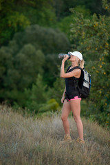 female hiker drinking water in forest at sunset, Adventure, travel, tourism.