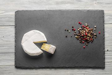 Камамбер с перцем на каменной доске черного цвета