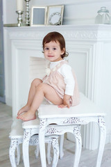 Sweet little girl at home sitting on modern chair relaxing in white living room