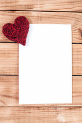 Heart and blank paper on wooden desk for Valentines day