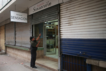 An employee closes the entrance to a store minutes before the start time of a curfew enforced by Honduras government while the country is still mired in chaos over a contested presidential election in Tegucigalpa