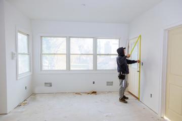 Carpenter brad using nail gun to moldings on doors, framing trim,