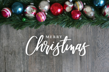 Wall Mural - Merry Christmas Calligraphy with Festive Colorful Holiday Christmas Ornament Border Over Garland and Wood Background
