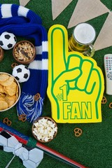 Foam hand, snacks and footballs on artificial grass