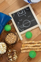 Strategy board, snacks and balls on wooden table