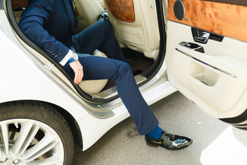 A man in an expensive blue suit out of sporty luxury cars. Sexy man sitting in car with front door open